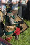 Russian warrior in iron helmet prepares to fight. Russian warrior in iron helmet and chained armour with wooden shield from medieval century prepares to fight Royalty Free Stock Images