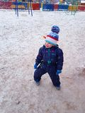 Russian winter and a boy. Russian winter. The town square. A little boy in a funny hat blue suit white snow royalty free stock image