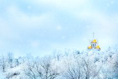 Russian winter landscape. Golden domes of the church against the background of a winter white forest. Snowing.  stock photo