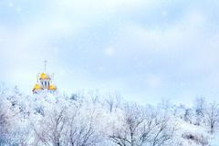 Russian winter landscape. Golden domes of the church against the background of a winter white forest. Snowing. Russian winter landscape. Golden domes of the royalty free stock photography