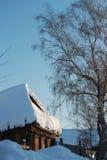 Russian winter in village. The disintegrating house under snowdrift Stock Photos