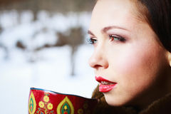 Russian woman in a coat. Russian girl drinking tea in the village royalty free stock images