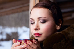 Russian woman in a coat. Russian girl drinking tea in the village royalty free stock photography