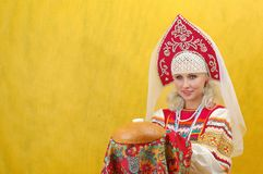 Russian woman in a folk russian dress. Holds a bread on yellow background Royalty Free Stock Photo