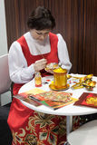 Russian woman painting a matryoshka at Bit 2014, international tourism exchange in Milan, Italy Royalty Free Stock Images