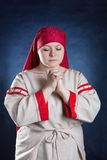 Russian woman praying in national clothes Royalty Free Stock Photo