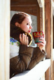 Russian woman in a scarf and coat. Russian woman drinking tea with closed eyes royalty free stock image