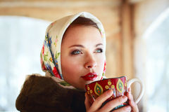 Russian woman in a scarf and coat. Russian girl drinking tea in the village Royalty Free Stock Photos