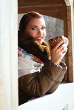 Russian woman in a scarf and coat. Russian woman holding a cup and smiling in a village Stock Image