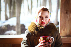 Russian woman in a scarf. And coat holding a cup and smiling in a village stock images