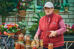 Russian woman selling rolled into cans vegetables (Kaluga region). Stock Photos