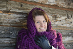 The Russian woman in  shawl warms hands near an. The Russian woman in a shawl warms hands near an izba Stock Photography