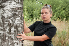 Russian  woman stands of birch Stock Image