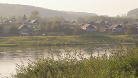 Russian wood village situated on banks of river in morning sun. Single-storey wooden houses with open white and blue shutters, outbuildings and fences, poles stock video footage