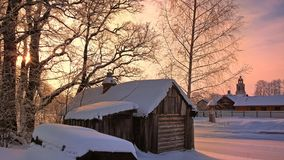 Russian wooden bathhouse in the frosty winter. Sunset hour Royalty Free Stock Image