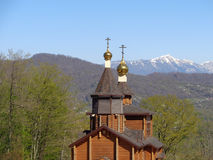 Russian wooden church among green trees Stock Photo