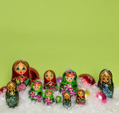 Russian wooden dolls with snow and Christmas balls Stock Photos