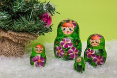 Russian wooden dolls with snow and Christmas tree Royalty Free Stock Photos