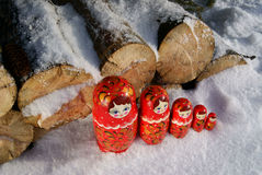 Russian wooden dolls on the snow  near firewood. Matryoshka - Russian wooden dolls on the snow  near firewood Royalty Free Stock Photo