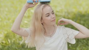Russian young blonde girl is combed sitting on the grass in the park. stock footage