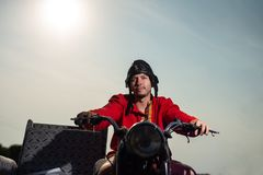 Russian motorcyclist on old Soviet motorcycle on sky background stock images
