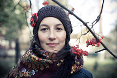 Russian young woman under the rowan branch. (Close-up  of Russian young woman dressed in dark coat, knitted cap and shawl with flower pattern, standing under the Stock Photos