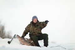 Russin Spearfishing met speargun schoot een grote vis onder het ijs Stock Afbeeldingen