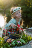 Russisch meisje in nationale kleding en een kroon van bloemen die op een de zomeravond zitten op de banken van de rivier royalty-vrije stock foto's