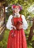 Russisch meisje in nationale kleding met een kruik melk Stock Afbeeldingen