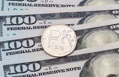 Russisch roebelmuntstuk over Amerikaanse dollarsbankbiljetten Royalty-vrije Stock Afbeelding