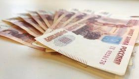 Russisch uit gewaaid geld, 5 duizendste nota's stock afbeelding