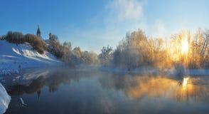 Russische Aard - de Winterzonsopgang op de rivierbank met de Orthodoxe Kerk stock afbeelding