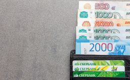 Russische bankbiljetten in benamingen van 1000, 2000 en 5000 roebels en creditcards Sberbank in een zwart close-up van de leerbeu Stock Afbeelding