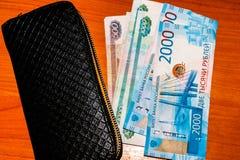 Russische bankbiljetten en zwarte portefeuille op de lijst stock foto