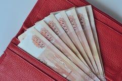Russische bankbiljetten 5000 roebels in rode vrouwenportefeuille stock foto