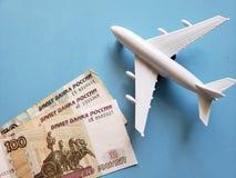 russische Banknoten, weißes Plastikflugzeug und blauer Hintergrund lizenzfreie stockfotos