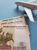 russische Banknoten, weißes Plastikflugzeug und blauer Hintergrund lizenzfreies stockbild
