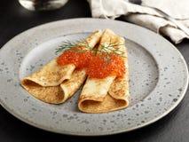 Russische Blinis mit rotem Kaviar auf einer grauen Plattennahaufnahme Lizenzfreie Stockfotos