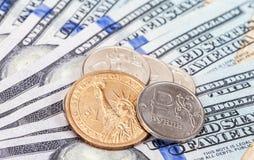 Russische en Amerikaanse muntstukken over dollarsbankbiljetten Stock Fotografie
