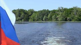 Russische Flagge auf dem Heck des Schiffs Wellen und Spuren auf dem Wasser Fluss oder See an einem Sommertag Blauer Himmel stock footage