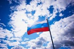 Russische Flagge auf dem Hintergrund des hellen Himmels mit volumetrischen Wolken patriotisch lizenzfreies stockbild