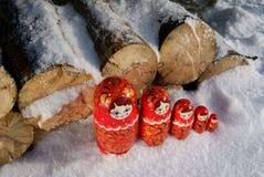 Russische hölzerne Puppen auf dem Schnee nahe Brennholz Lizenzfreies Stockfoto