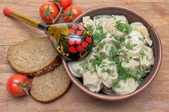 Russische Küche: Mehlklöße auf einer Platte, Kirschtomaten und Brot Lizenzfreies Stockfoto