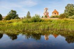 Russische Landschaft mit ruhigem Fluss und alter Kirche im Th Stockfotografie