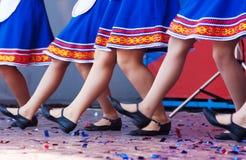Russische Mädchen in den traditionellen Kostümen, die auf Stadium tanzen Lizenzfreie Stockfotos