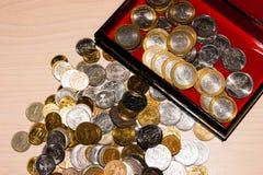 Russische Münzen von verschiedenen Bezeichnungen liegen in einem Haufen auf dem Tisch, nahe bei einer Schatulle mit Münzen lizenzfreie stockfotografie