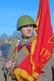 Russische militair-reenactor die een rode vlag houden Royalty-vrije Stock Fotografie