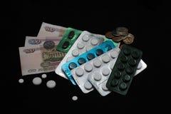 Russische muntstukken, bankbiljetten en pillen op zwarte achtergrond Royalty-vrije Stock Fotografie