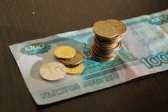 Russische muntstukken op een bankbiljet in de roebels van 1000 Royalty-vrije Stock Afbeeldingen