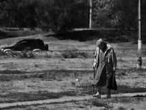 Russische oudsten - slecht geklede oude vrouw met een het lopen riet Stock Foto's